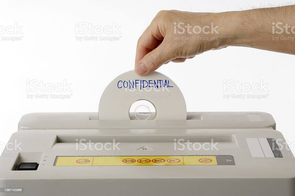 Confidential CD put into a paper shredder against white background stock photo