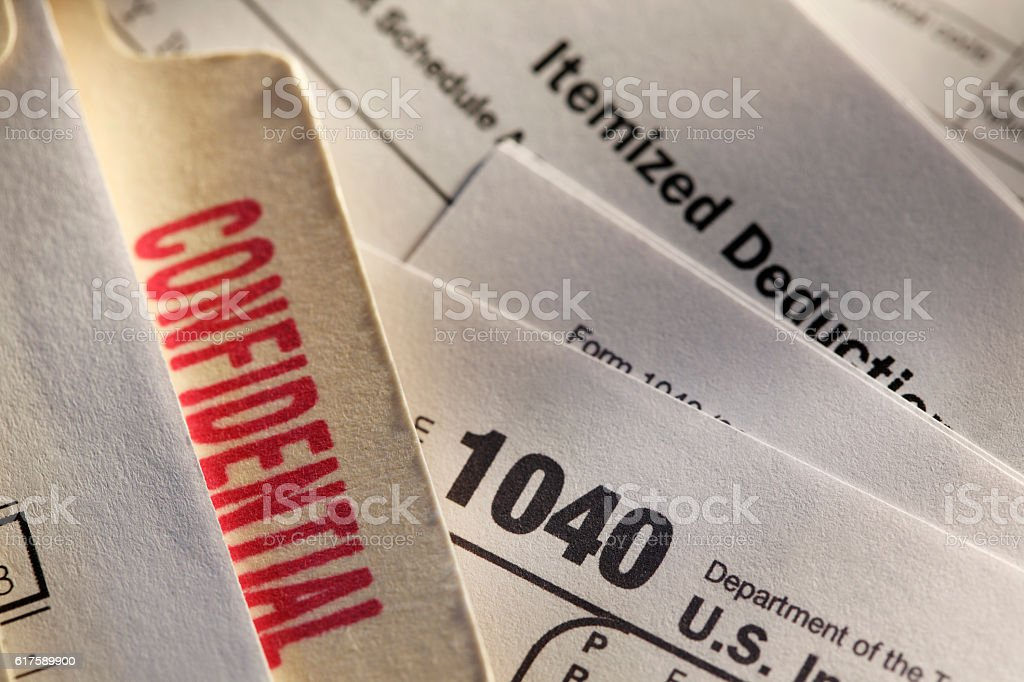 Confidential File Folder On Top Of An IRS Form 1040 stock photo