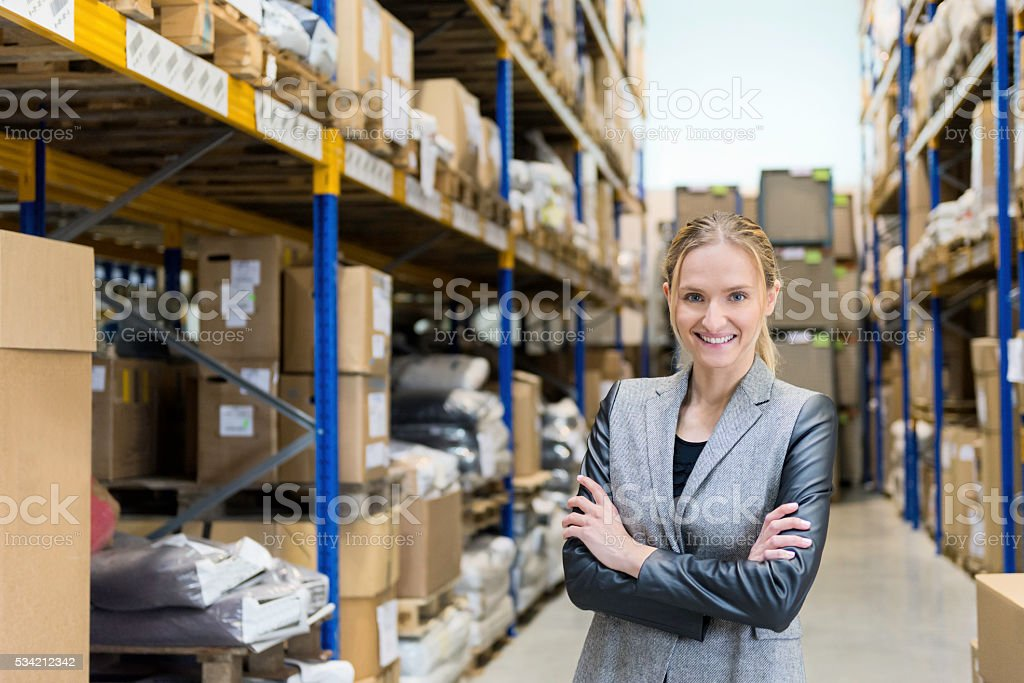 Confidential woman smiling in warehouse stock photo