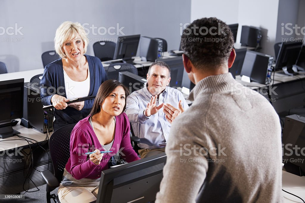 Confused adult students asking questions in computer lab stock photo