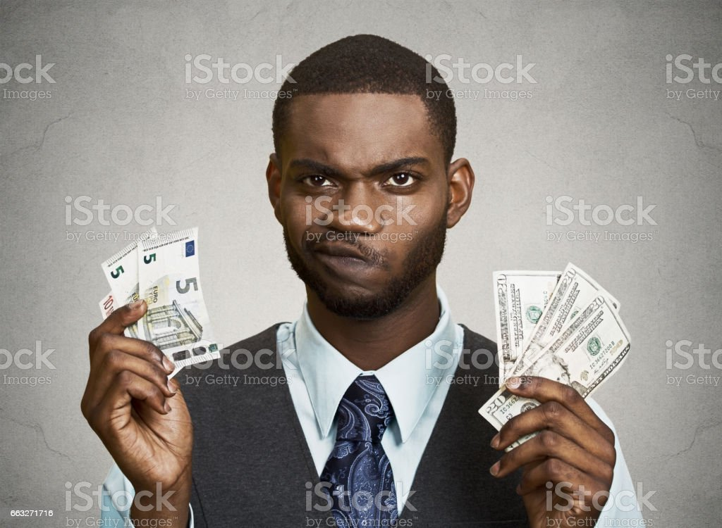 confused, business man standing, holding dollar and euro bills in hands stock photo