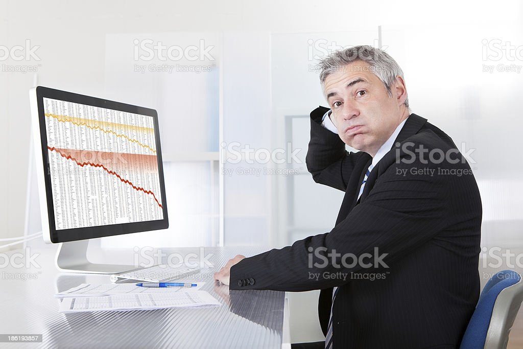 Confused businessman looking at graphs on a computer royalty-free stock photo