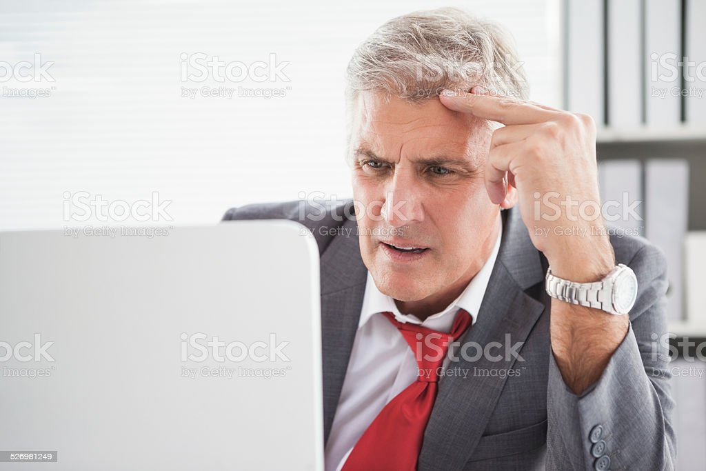 Confused businessman looking at his laptop stock photo