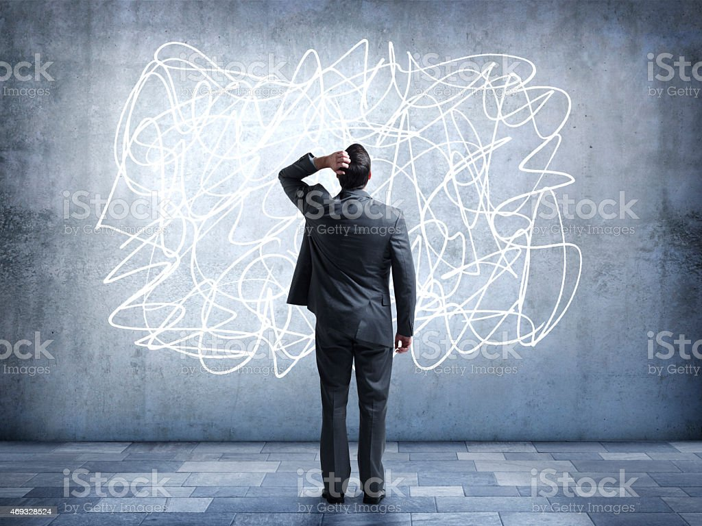 Confused businessman staring at scribble on wall stock photo