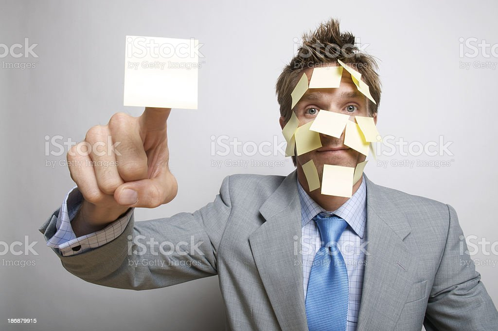 Confused Businessman with Face Covered in Yellow Sticky Notes Reminders royalty-free stock photo