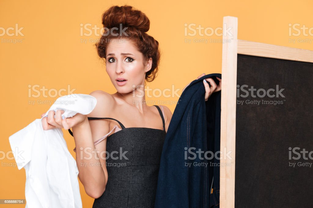Confused cute young woman choosing clothes behinf golding screen stock photo