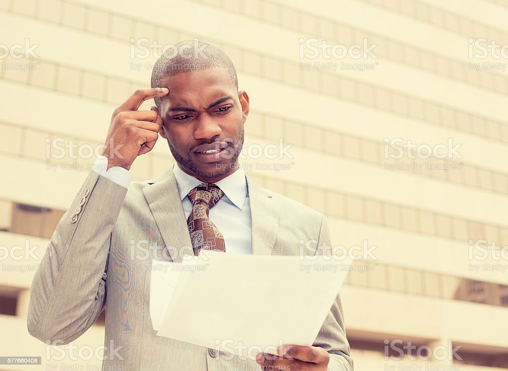 Confused executive man looking at documents stock photo