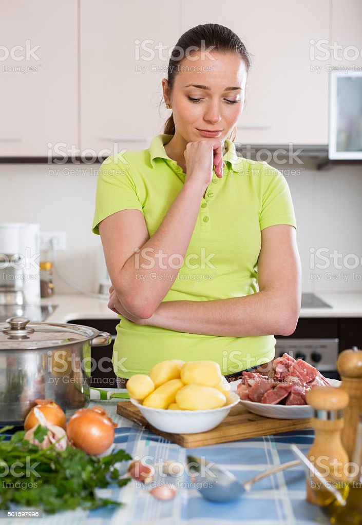 Confused housewife at kitchen stock photo