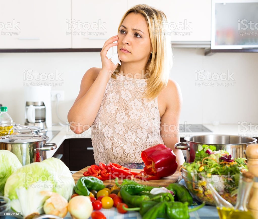 Confused housewife in the kitchen stock photo