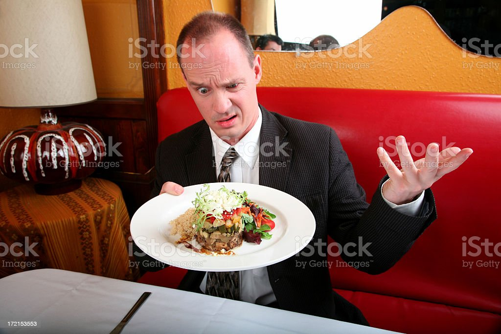 Confused man holding a plate of food in a restaurant stock photo