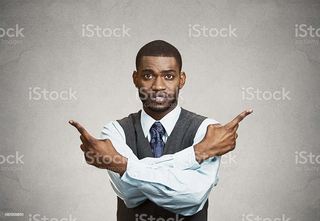 Confused man pointing in two different directions stock photo