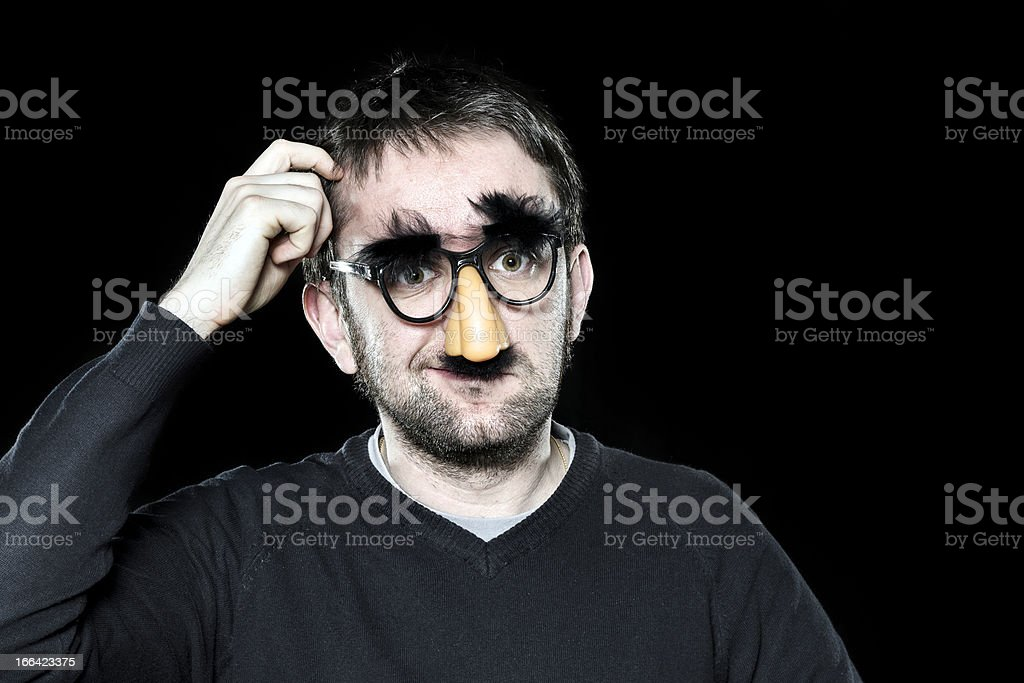 Confused man with fake nose, glasses, moustache and eyebrows stock photo