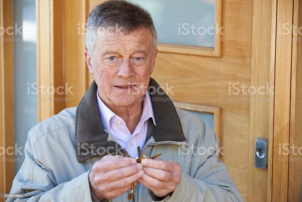 Confused Senior Man Trying To Find Door Key stock photo