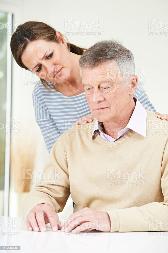 Confused Senior Man With Adult Daughter At Home stock photo