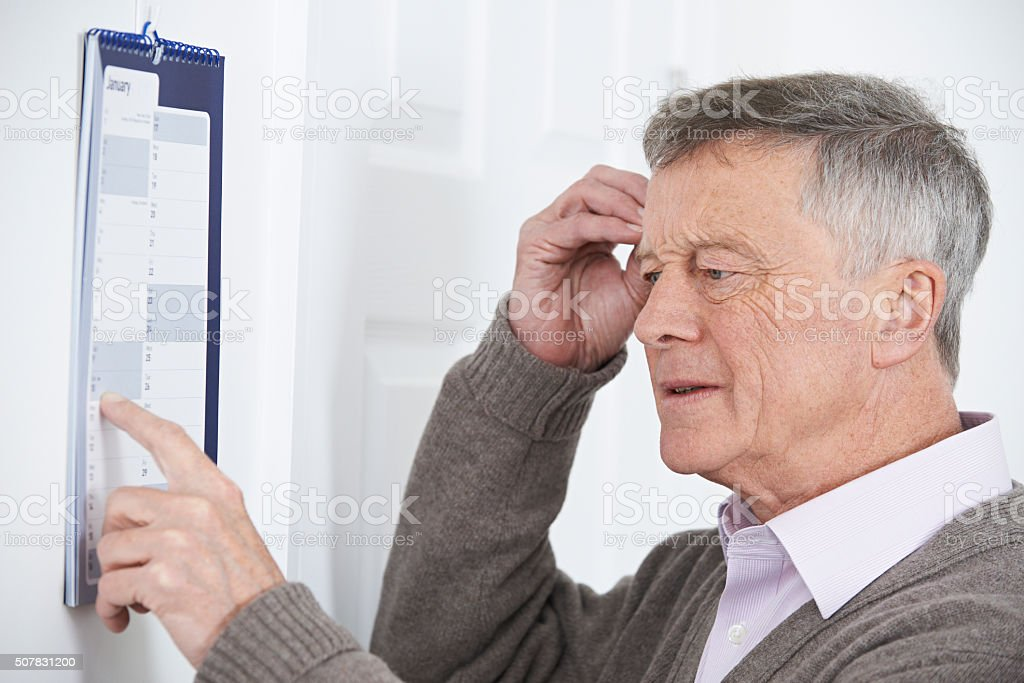 Confused Senior Man With Dementia Looking At Wall Calendar stock photo
