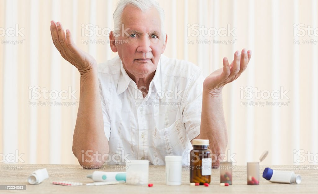 Confused senior man with variety of pills on table royalty-free stock photo