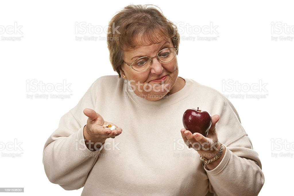 Confused Senior Woman Holding Apple and Vitamins royalty-free stock photo