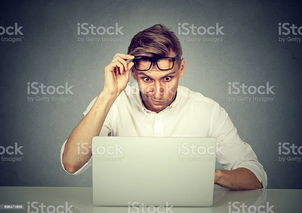 Confused shocked man looking at his laptop stock photo