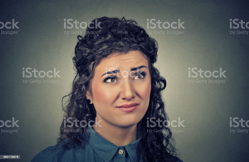 confused skeptical young woman thinking looking up stock photo