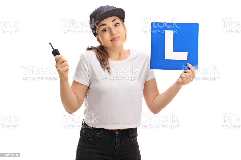 Confused teen girl holding a car key and an l-sign stock photo