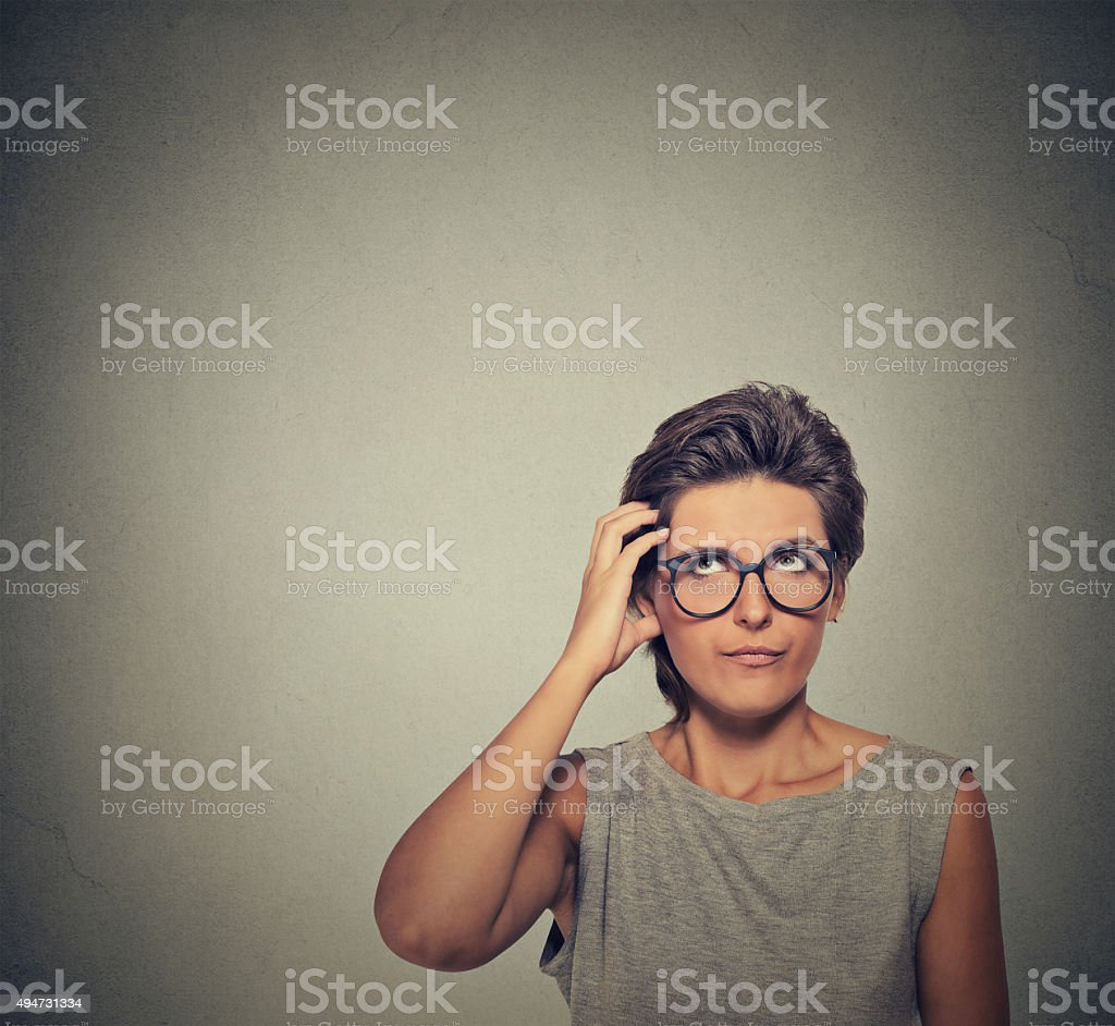 Confused thinking woman in glasses bewildered stock photo