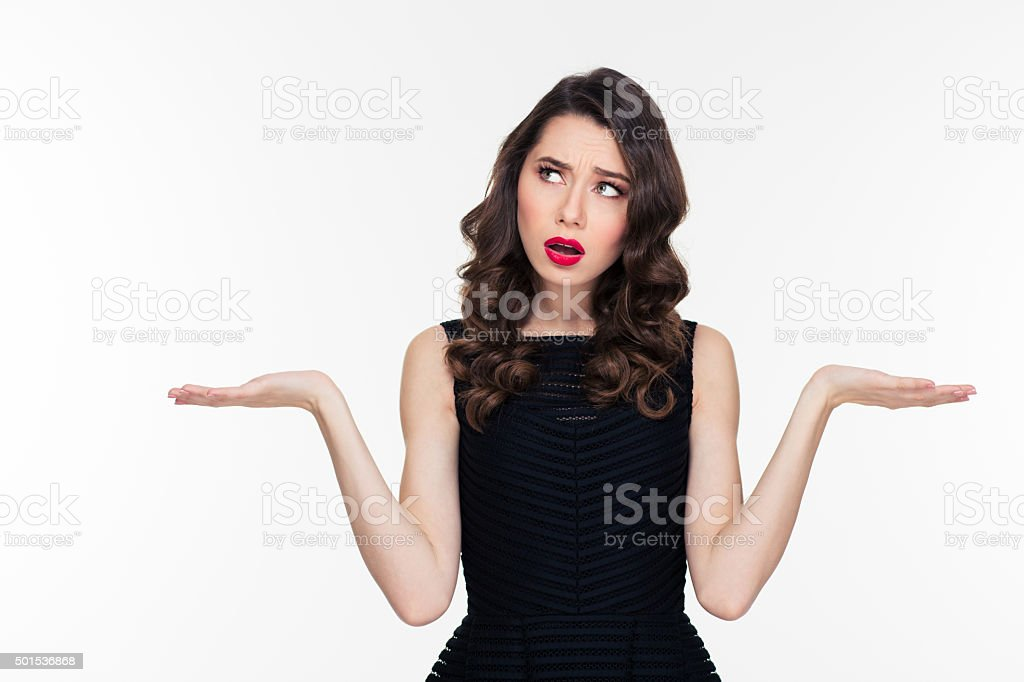 Confused thoughtful curly young woman holding copyspace on both palms stock photo