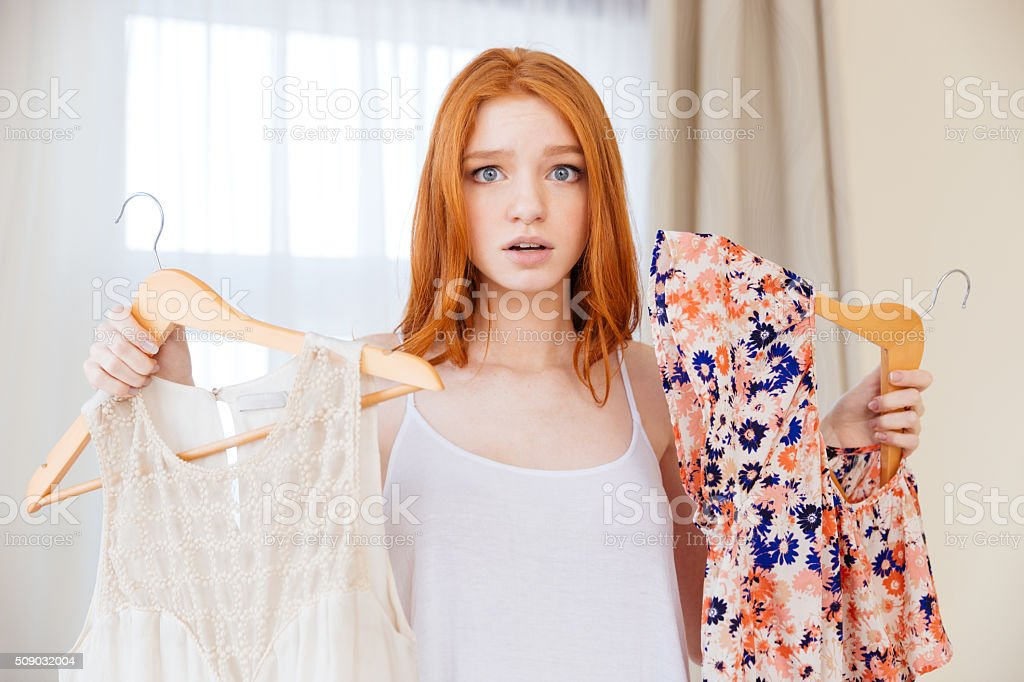 Confused woman choosing between two dresses stock photo