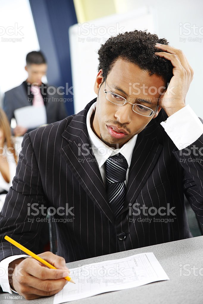 confused young black business man with colleagues in modern office royalty-free stock photo