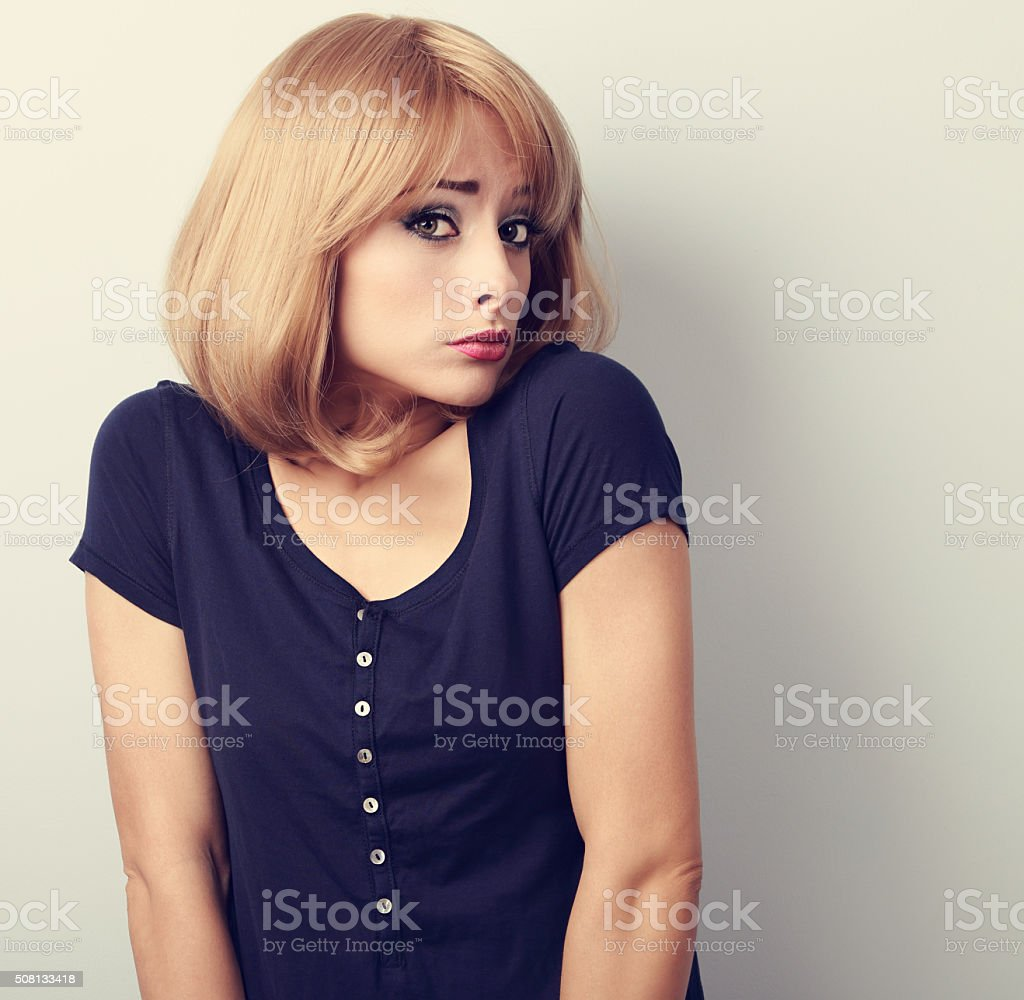 Confused young casual woman with blond hair. Toned closeup stock photo