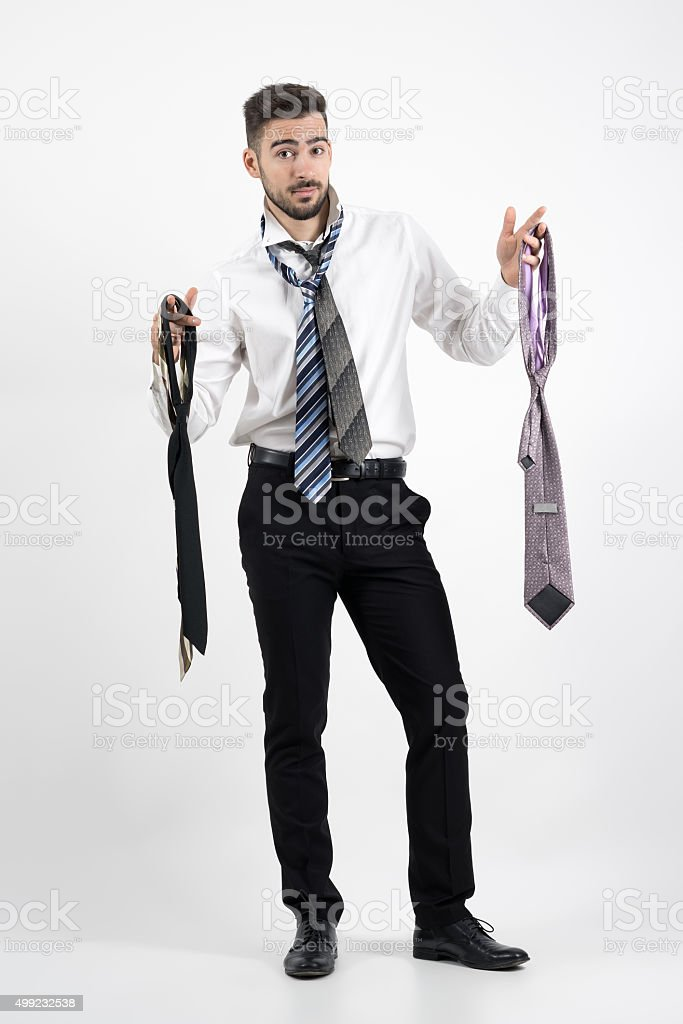 Confused young man trying to choose right necktie. stock photo