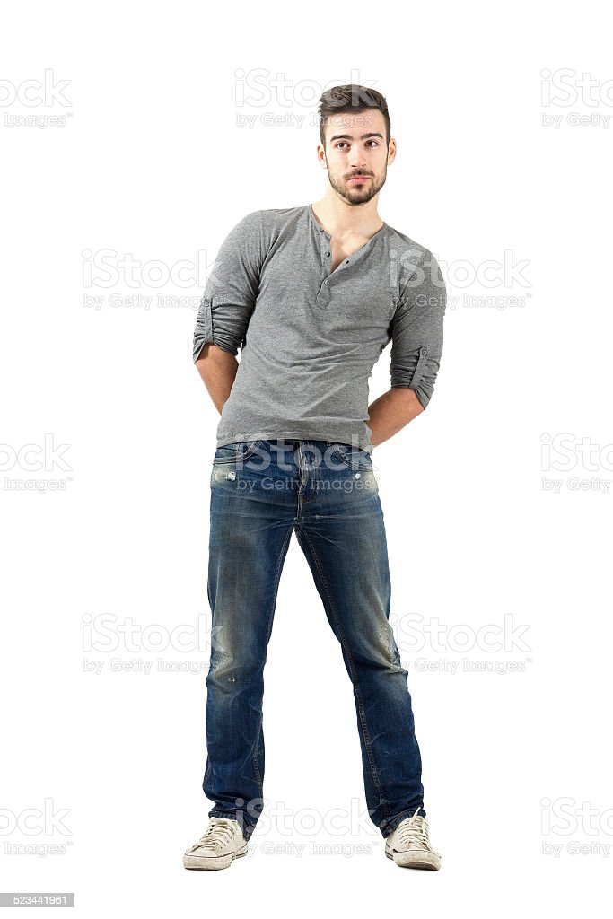 Confused young man with hand clasped on his back stock photo