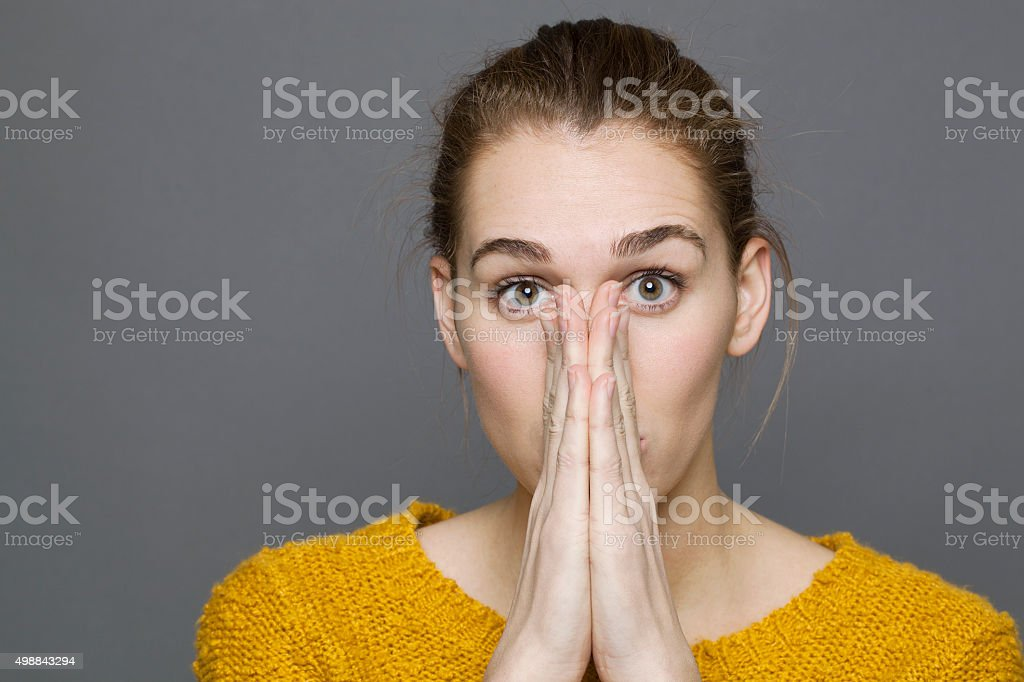 confused young woman joining hands flat together for stunning mistake stock photo