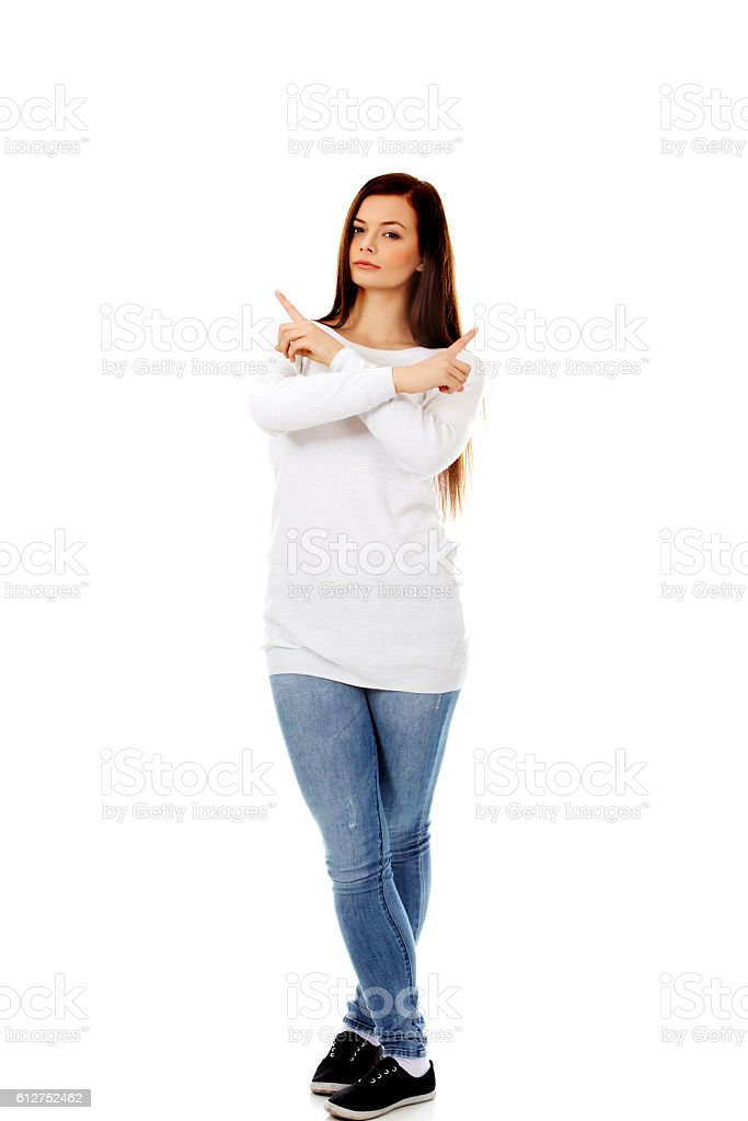 Confused young woman pointing in two different directions stock photo