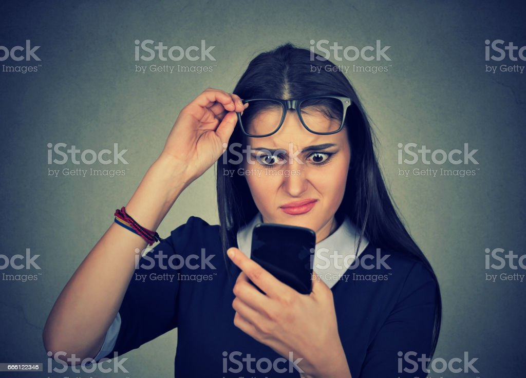 confused young woman with glasses having trouble seeing cell phone stock photo