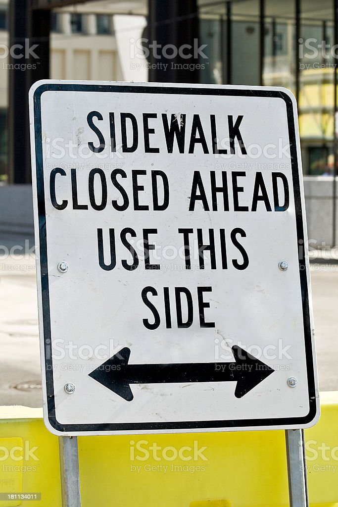 Confusing sign reading sidewalk closed ahead use this side royalty-free stock photo