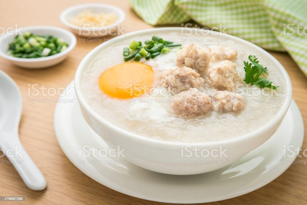 Congee with minced pork and boiled egg in bowl stock photo