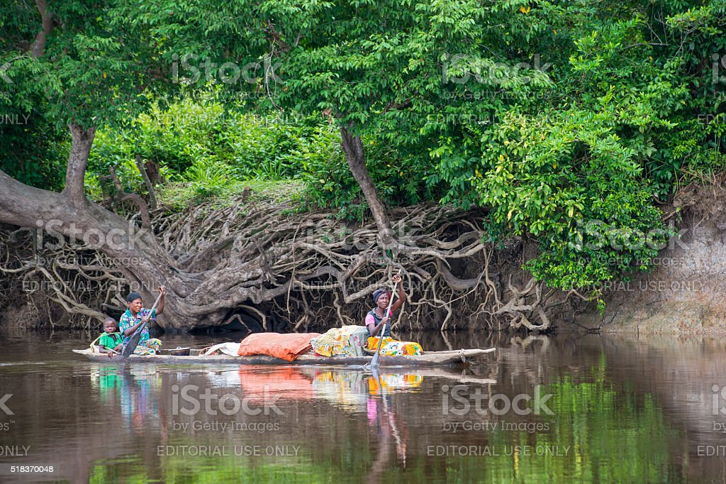 Congolese women are paddling in a pirogue on Congo River stock photo