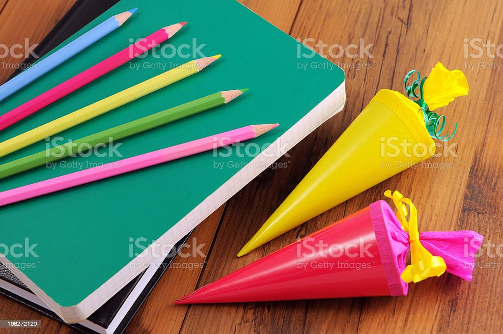 Conical bag of sweets with crayons work book school stock photo