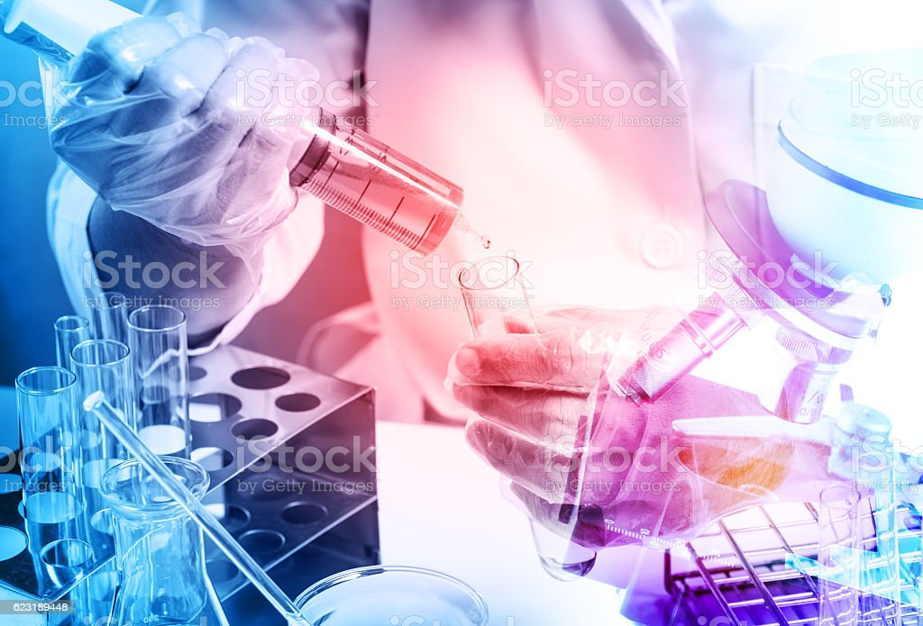 Conical flask in scientist hand with lab glassware background, stock photo