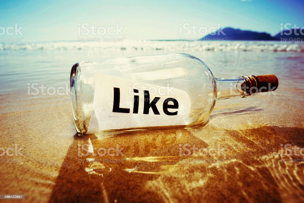 Connected castaway sends message in bottle reading 'like' stock photo