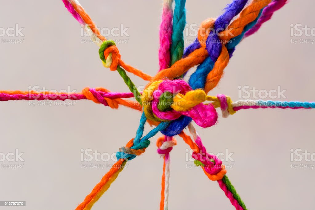 Connected group concept as many different ropes tied and linked stock photo