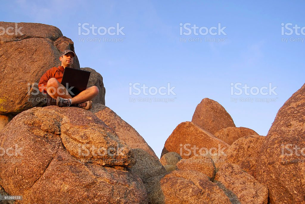 connected: man in the sunset boulder landscape with computer stock photo