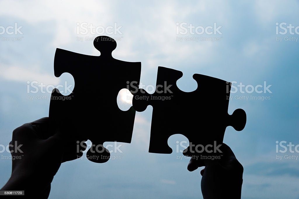 Connecting two jigsaw puzzle stock photo