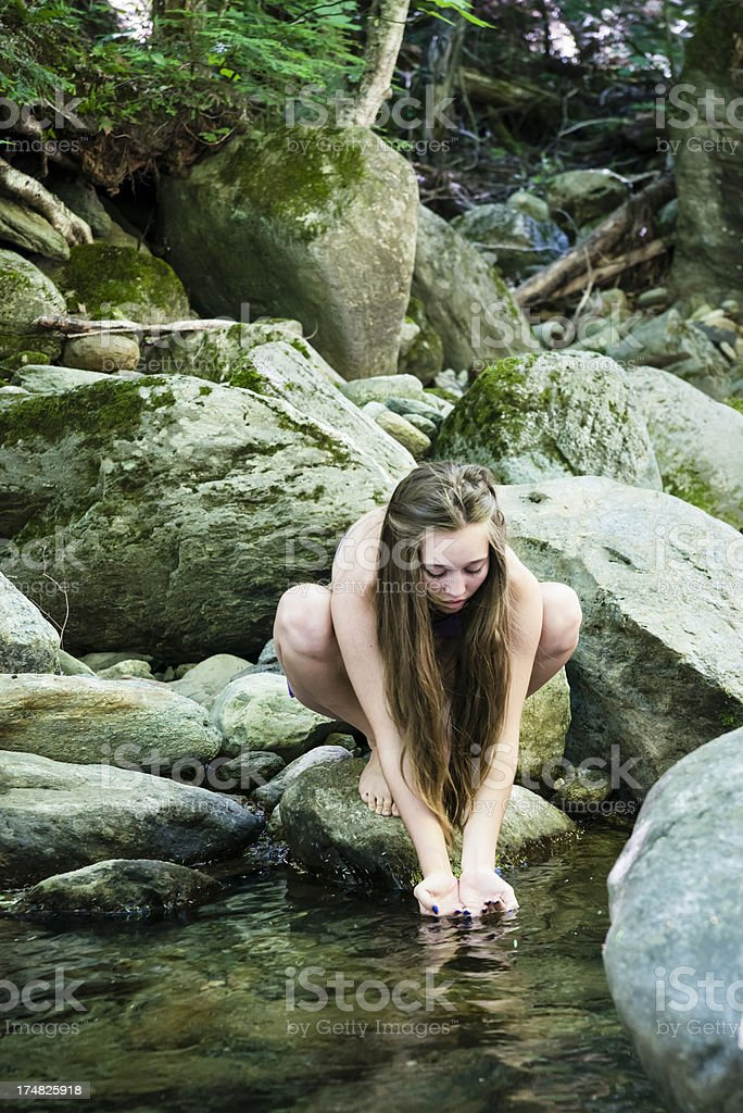 Connecting with nature, girl and streaming water. royalty-free stock photo