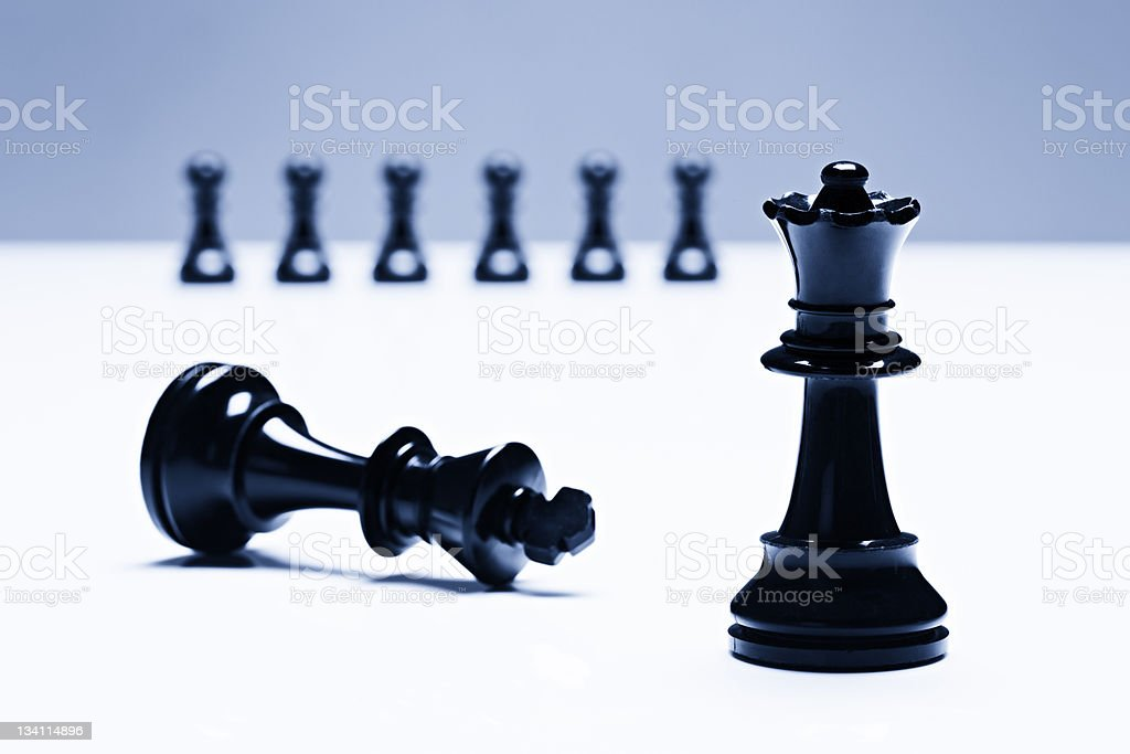 Conquered chess king lies at queen's feet, observed by pawns royalty-free stock photo