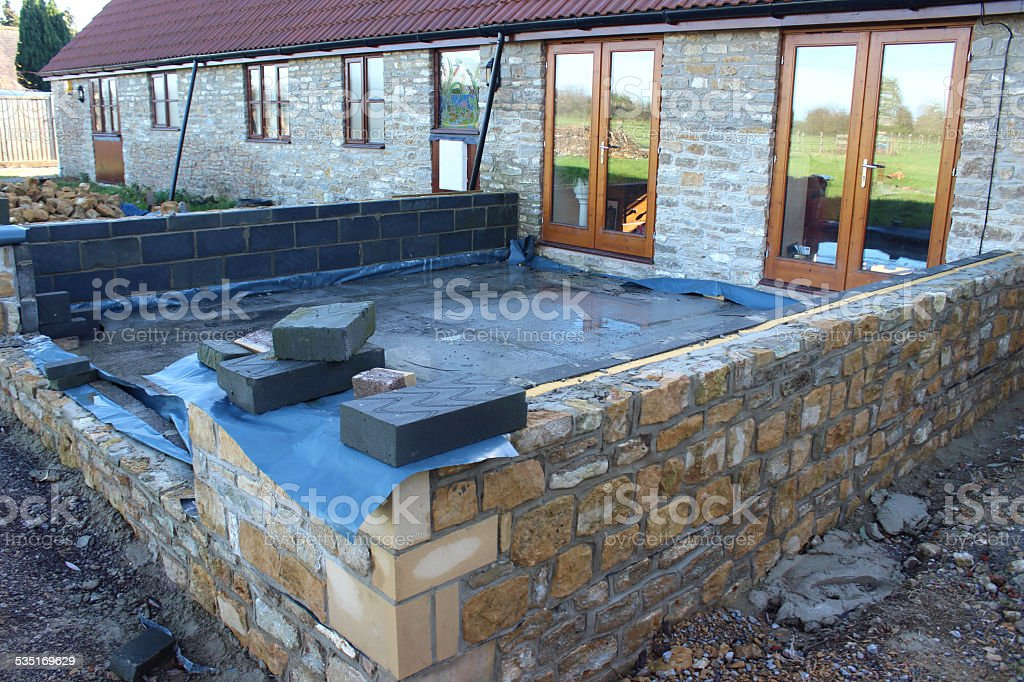 Conservatory foundations / stone wall being built behind bungalow barn conversion stock photo