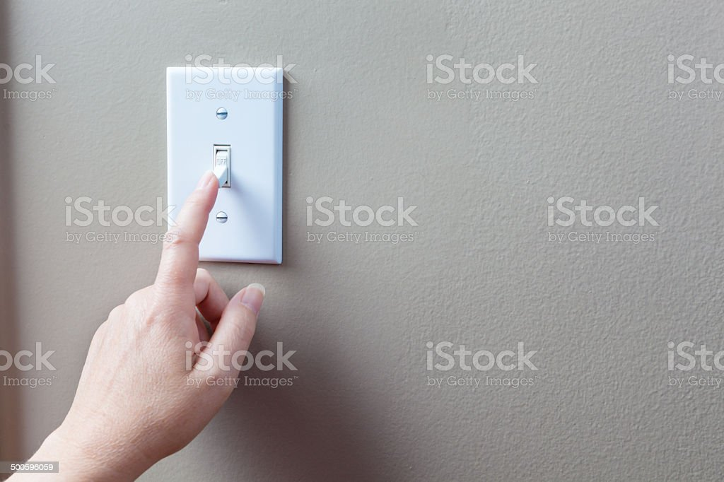 Conserving Eletricity Energy by Turning Off Light Switches Horizontal stock photo