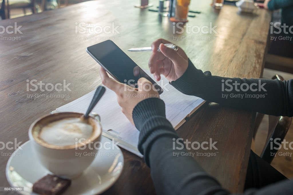 Considering whether to make phone-call while sitting at coffee shop stock photo