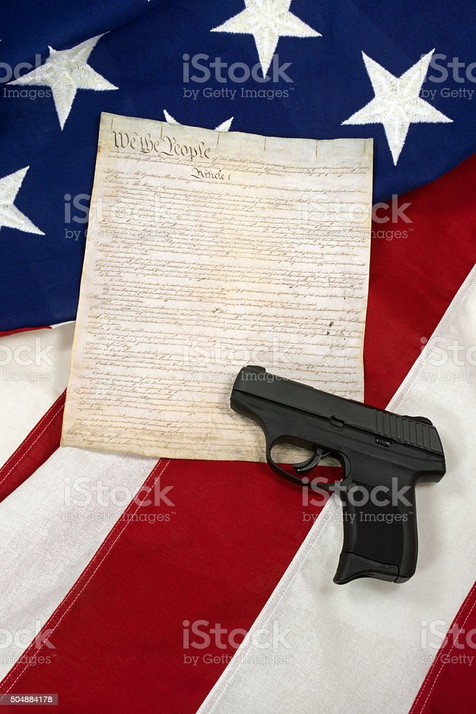 Constitution with Hand Gun on American Flag, Vertical stock photo