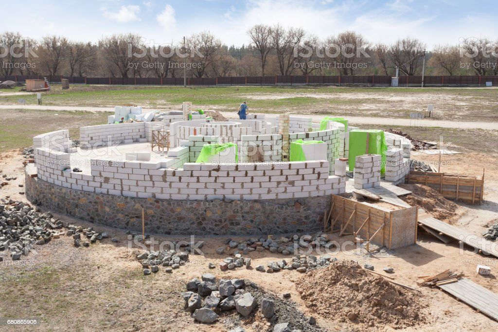 Constraction workers building a roundhouse with aerated autoclaved concrete blocks stock photo